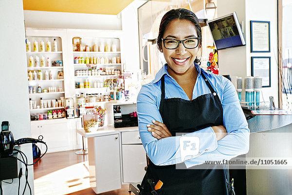 Smiling Hispanic hairdresser posing in hair salon