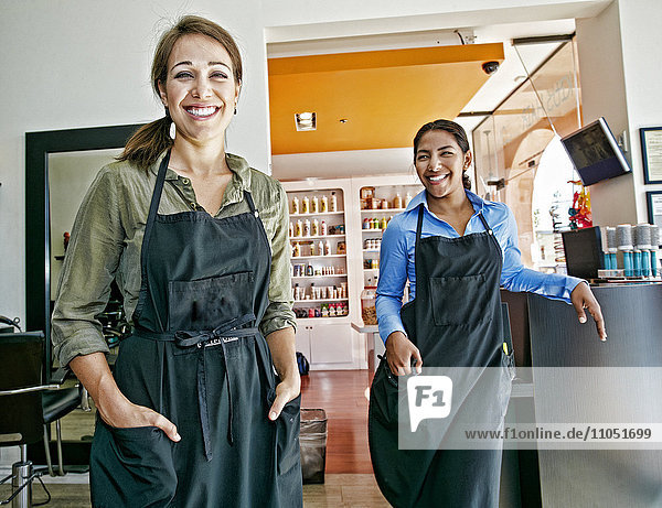 Smiling hairdressers posing in hair salon