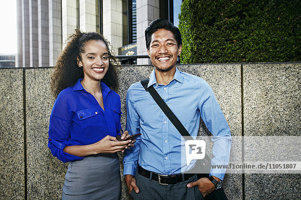 Smiling businesspeople posing outdoors