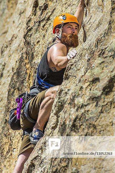 Caucasian man climbing rock