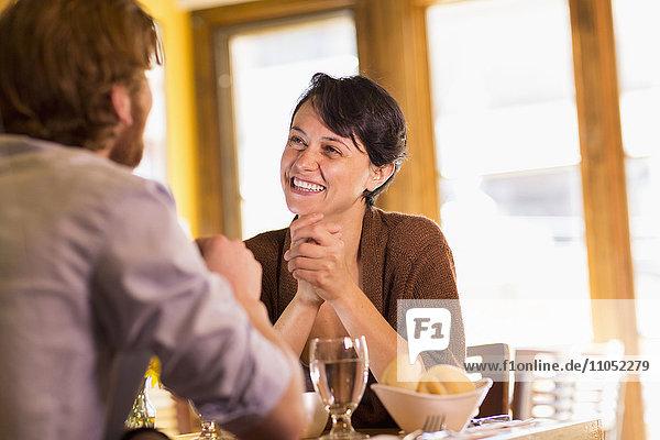 Caucasian couple talking in restaurant