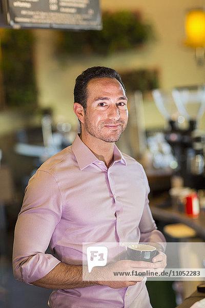 Hispanic businessman drinking coffee in coffee shop
