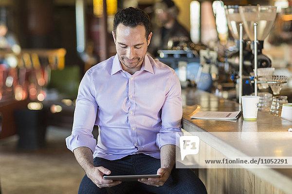 Hispanic businessman using digital tablet in coffee shop