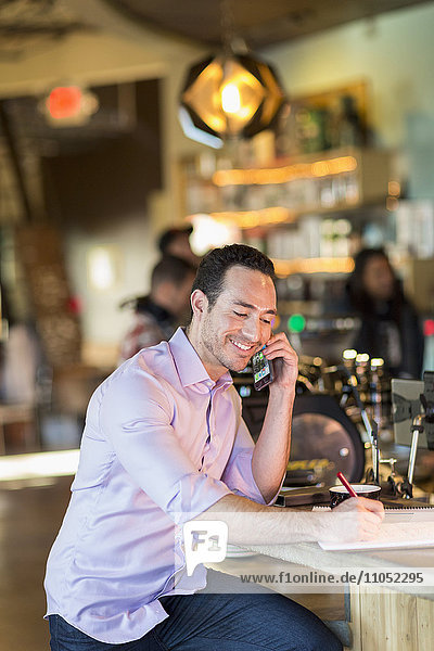 Hispanic businessman talking on cell phone in coffee shop