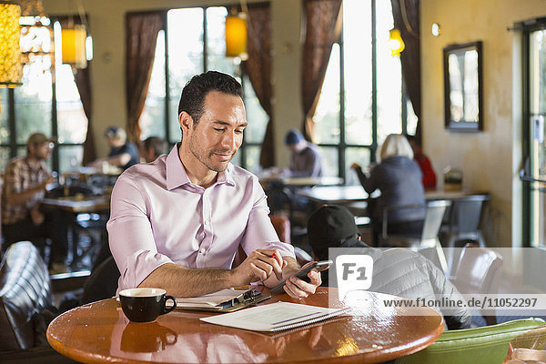 Hispanic businessman using cell phone in coffee shop