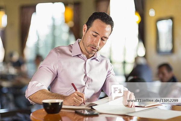 Hispanic businessman writing in coffee shop
