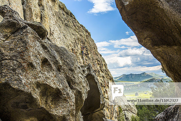 Distant Caucasian woman climbing rock