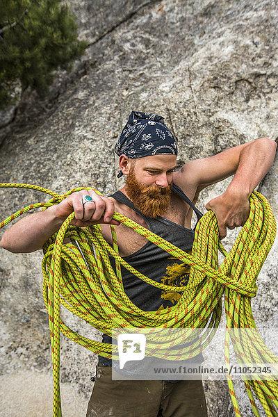 Caucasian man winding rope