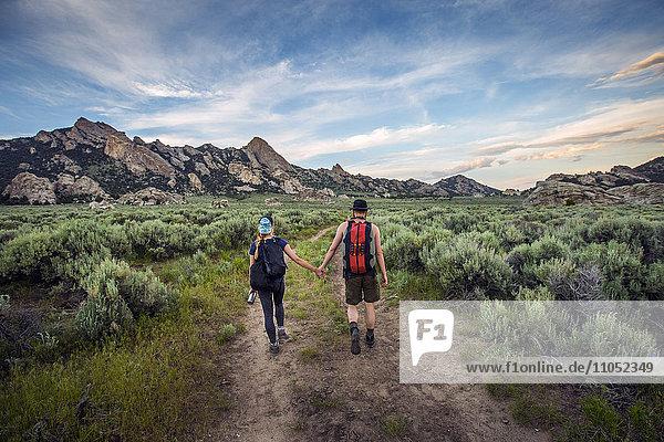 Caucasian couple hiking toward mountain