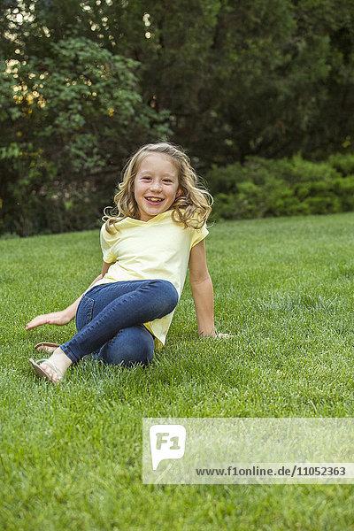 Smiling Caucasian girl sitting in grass