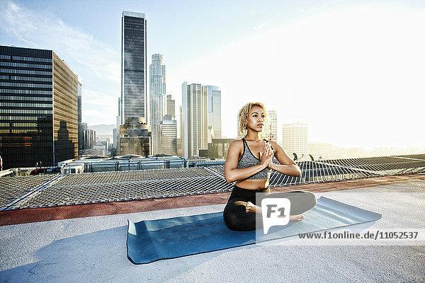 Mixed race woman meditating on urban rooftop