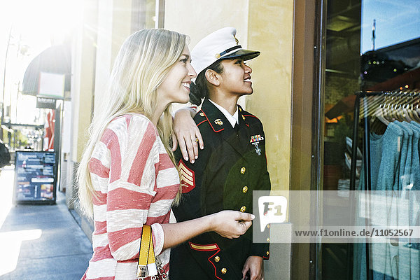 Asian soldier and friend window shopping