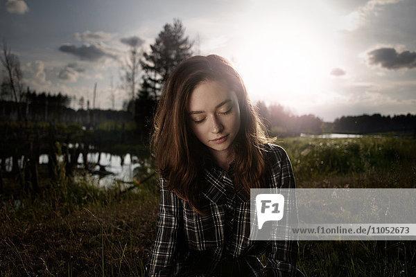 Pensive Caucasian woman in field near lake