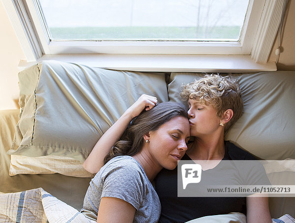 Caucasian lesbian couple kissing in bed