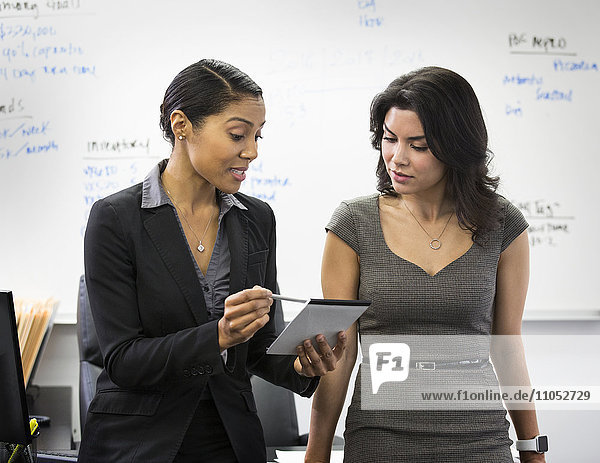 Businesswomen talking with notepad in office