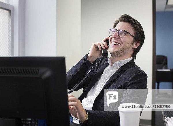 Caucasian businessman talking on telephone in office