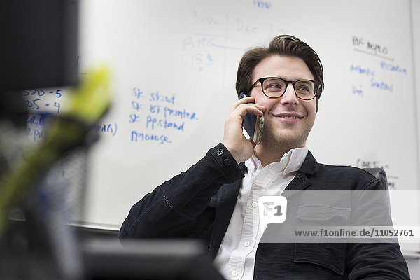 Caucasian businessman talking on cell phone in office