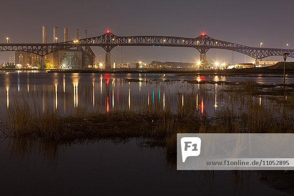 Reflection of illuminated bridge in still lake