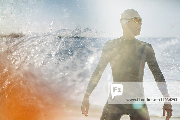 A swimmer in a wet suit standing by the water's edge.