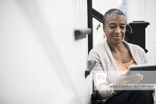 Eine reife Frau  die in einem Flur saß und ein digitales Tablett benutzte.