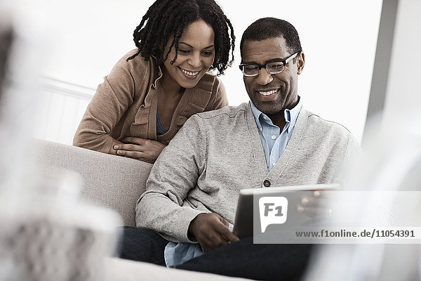 Ein Paar  Mann und Frau  die sich ein digitales Tablett teilen.
