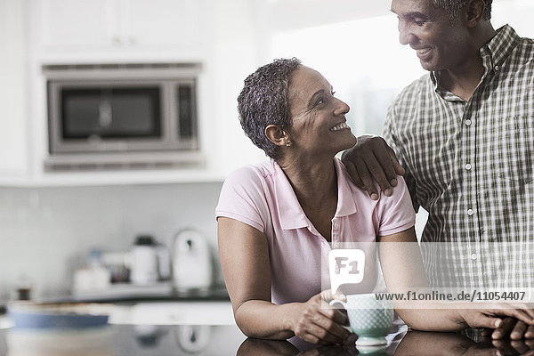 A couple in the kitchen of their home  smiling at each other.