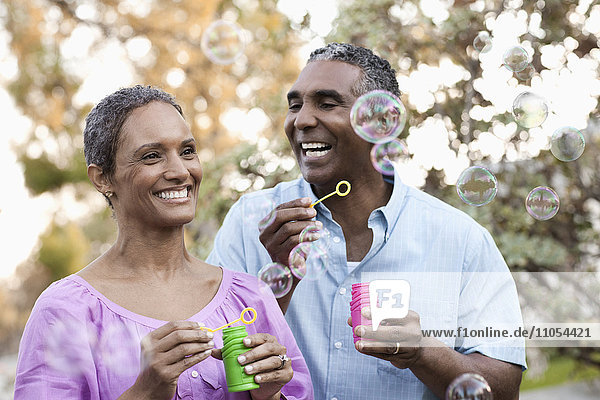 A mature couple  man and woman blowing bubbles celebrating an occasion outdoors.
