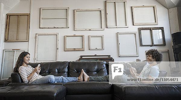 Loft-Dekor. Eine Wand  an der Bilder in Rahmen aufgehängt sind  die umgekehrt die Rückseiten zeigen. Ein junges Paar sitzt auf dem Sofa und berührt sich mit den Füßen  einer benutzt ein Smartphone und einer hält ein digitales Tablett.