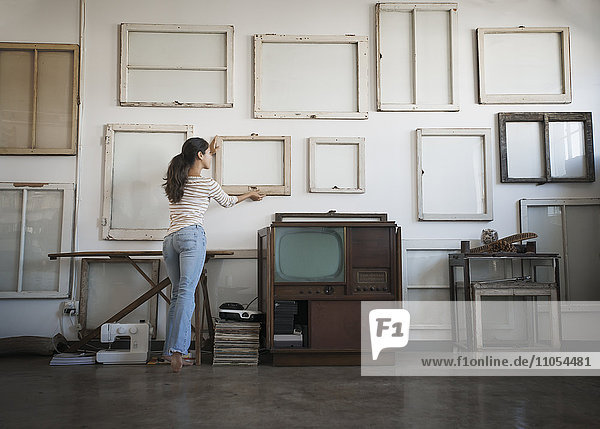 Loft decor. A woman hanging picture frames  blank canvases on a wall.