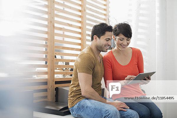 Ein Paar  das mit einem digitalen Tablett am Fenster sitzt.
