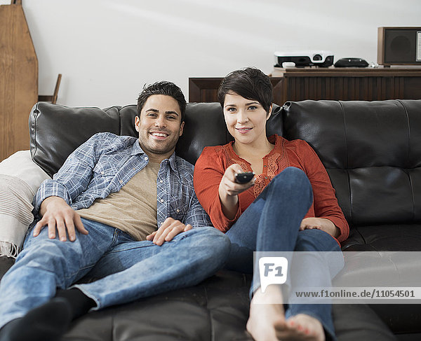 A man and woman sitting on a sofa  side by side  one using the remote control for the tv.