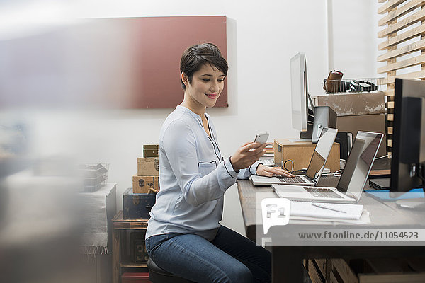 A woman in a home office with a desk with two laptops  checking her smart phone.
