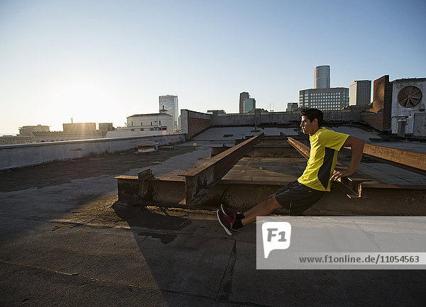 A man in exercise clothes on a rooftop overlooking the city  doing bench shoulder push ups.