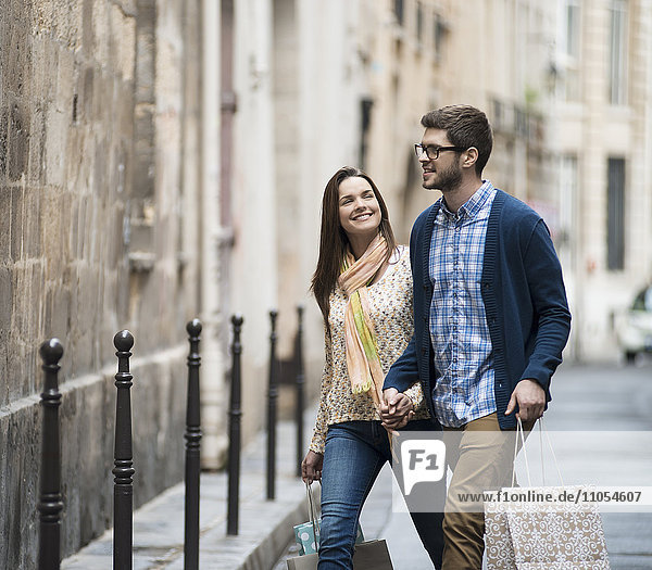 A couple walking along a narrow city street with shopping bags.