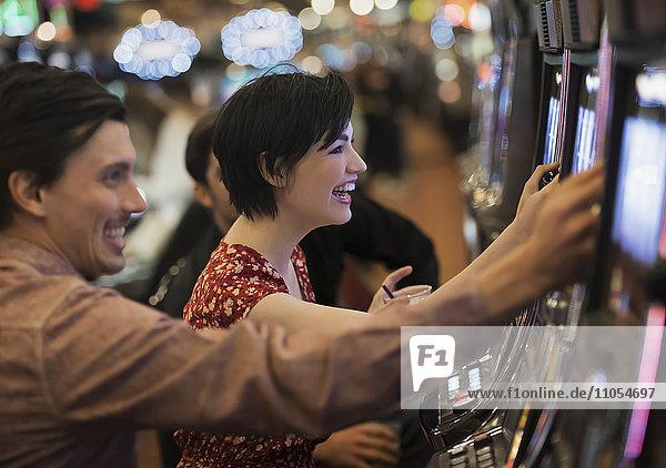Zwei Personen  ein junger Mann und eine Frau  spielen in einem Kasino an den Spielautomaten.