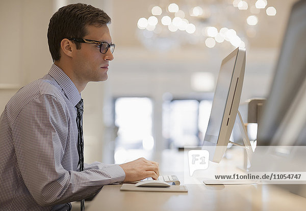 A businessman in shirt and tie seated at a computer in a business centre or office.