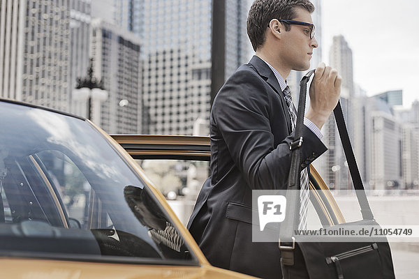 A working day. Businessman in a work suit and tie with a computer bag getting out of a taxi.