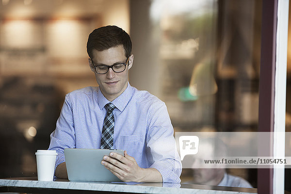 A working day. Businessman in a shirt and tie seated using a digital tablet in a cafe.