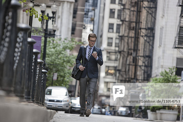 A working day. Businessman in a work suit and tie on a city street checking his smart phone.