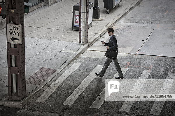 View from above of a man in the middle of a pedestrian road crossing  looking at his phone.