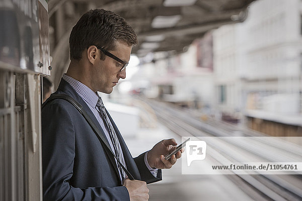 A working day. Businessman in a work suit and tie on a station platform  checking his phone