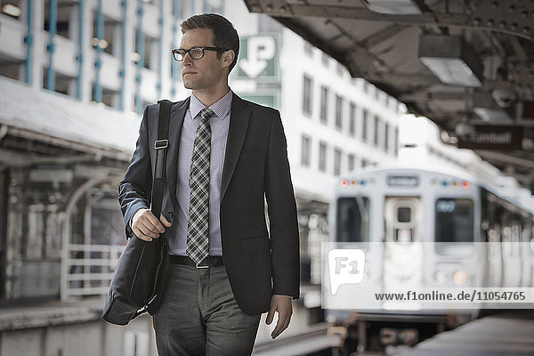 A working day. Businessman in a work suit and tie on a railway station platform.