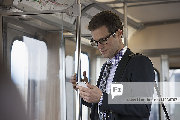 A working day. Businessman in a work suit and tie in a train carriage  checking his phone.