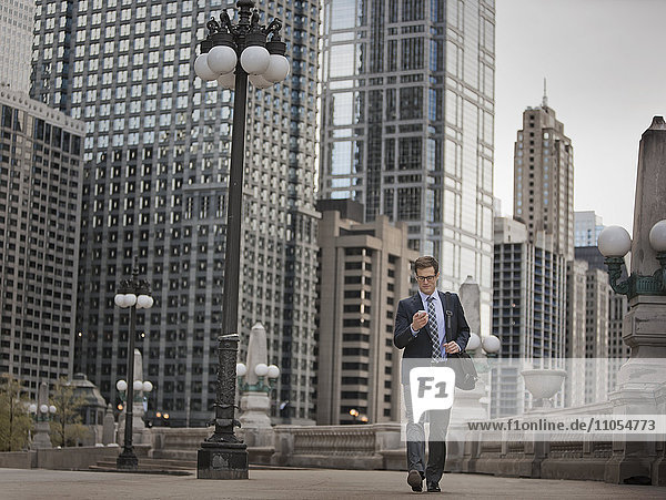 A working day. Businessman in a work suit and tie on a city street  checking his phone.