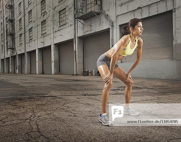 Eine Frau in Laufbekleidung,  Korboberteil und Shorts,  die ihren Körper streckt und sich auf einen Lauf vorbereitet oder sich nach dem Training abkühlt.