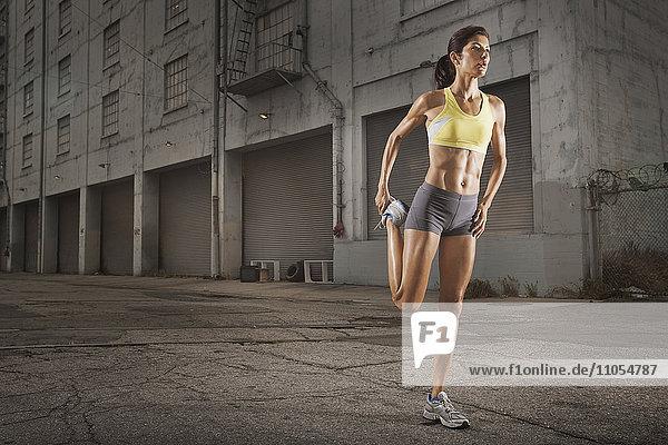 Eine Frau in Laufbekleidung  Korboberteil und Shorts  die ihren Körper streckt und sich auf einen Lauf vorbereitet oder sich nach dem Training abkühlt.