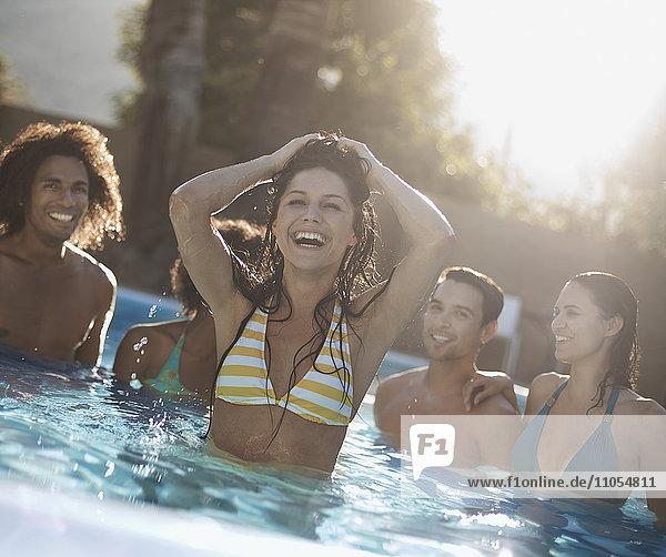 Eine Gruppe junger Männer und Frauen im Schwimmbad am Ende eines heißen Tages.