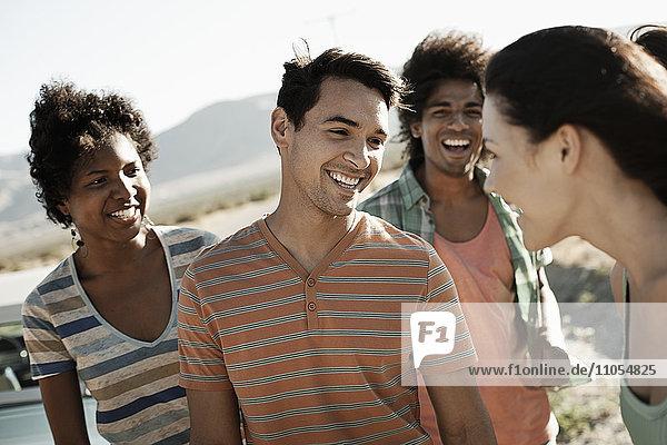Eine Gruppe von Freunden  Männer und Frauen  auf offener Straße  im Gehen und Sprechen.