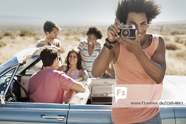 A group of friends by a pale blue convertible on the open road  on a flat plain surrounded by mountains  one holding a camera.
