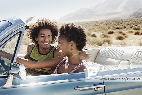 Ein junges Paar  Mann und Frau in einem hellblauen Cabriolet auf offener Straße